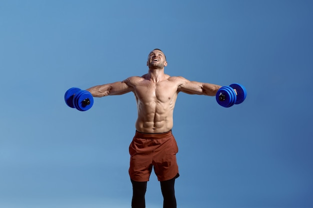 Male muscular athlete with dumbbells poses in studio, blue background. one man with athletic build, shirtless sportsman in sportswear, active healthy lifestyle