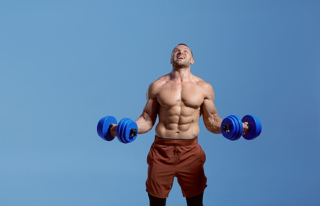 Male muscular athlete with dumbbells in studio
