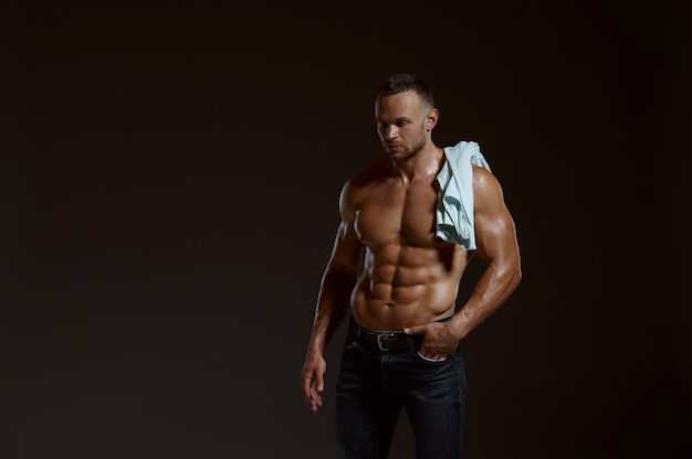 Male muscular athlete with shirt on his shoulder