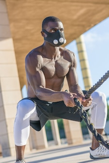 Male muscular training with battle ropes and training mask