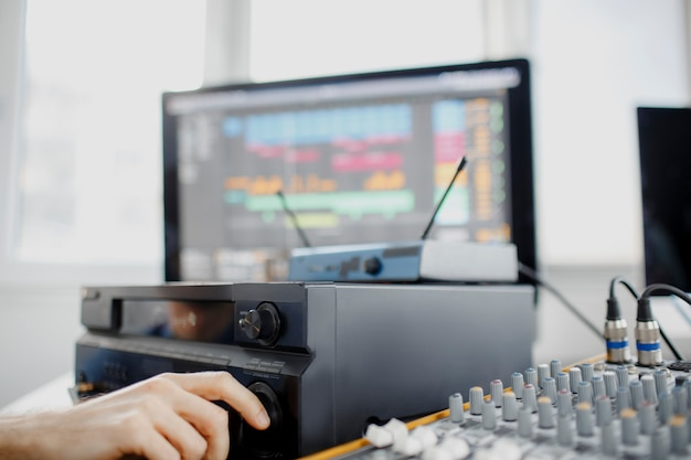 Male music arranger works with sound amplifier he is composing song on midi piano and audio equipment in digital recording studio. dj in broadcasting studio. music, technology and equipment concept.