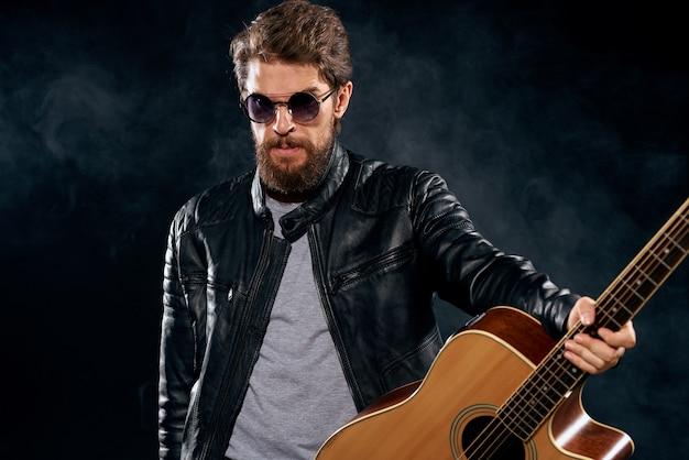 Музыкант в кожаной куртке в исполнении гитары музыкальной группы. фото высокого качества