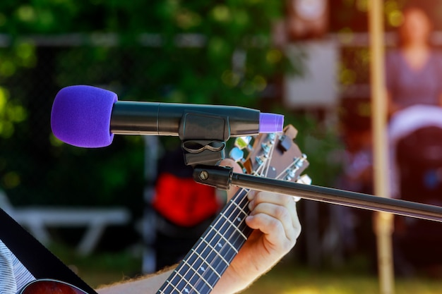 Male musician playing acoustic guitar behind condenser microphone in recording