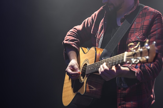 Male musician playing acoustic guitar in a dark room copy space.