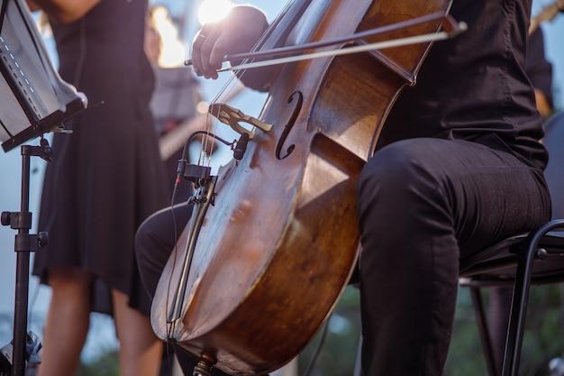 Музыкант играет на виолончели в оркестре на улице