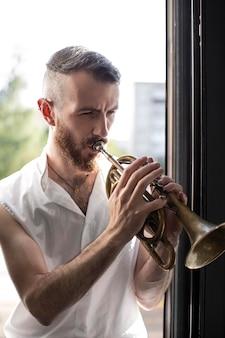 Мужчина-музыкант играет на корнете рядом с окном