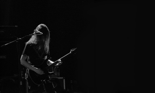 Male musician playing guitar on a stage near the microphone in black and white