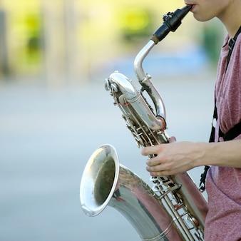 Мужской музыкант играет на саксофоне на улице