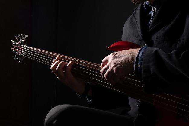 Мужской музыкант, играющий на шестиструнной безладовой бас-гитаре на темном фоне