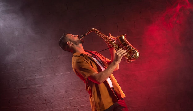 Мужской музыкант играет на саксофоне в тумане