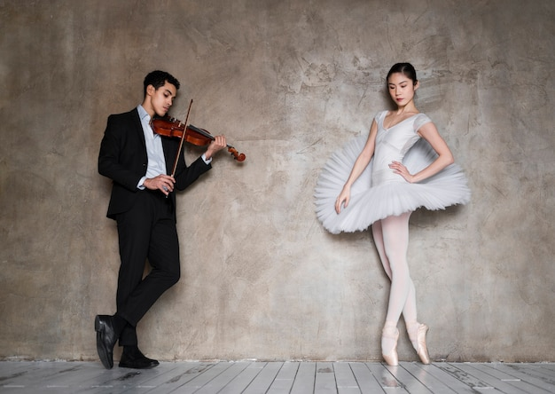 Male musician playing violin for ballerina