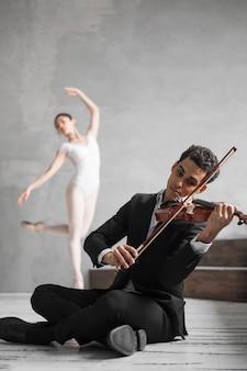 Male musician playing violin and defocused ballerina dancing
