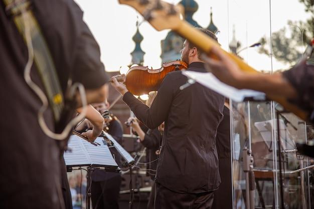 Мужской музыкант играет на скрипке в оркестре на открытом воздухе
