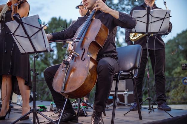 Мужской музыкант играет на виолончели в оркестре на улице