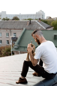 Male musician with cornet on roof top