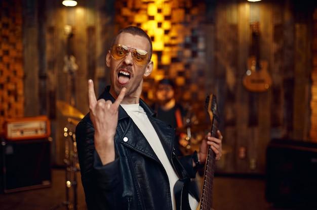 エレクトリックギターを持った男性ミュージシャン、バーのステージで演奏する音楽。ロックバンド演奏、ガレージでのコンサートの繰り返し、弦楽器を持つ男、ライブサウンドパフォーマー