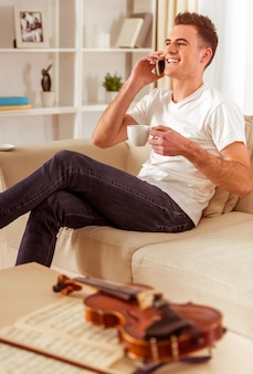 Male musician with a violin sitting on the sofa at home.
