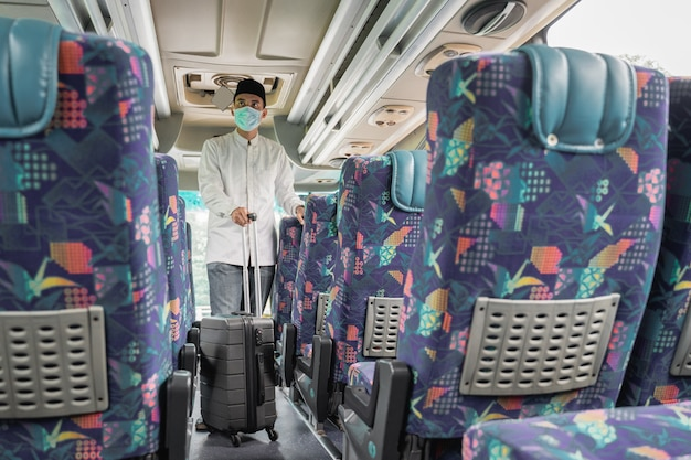 Male muslim travel by public bus during pandemic wearing mask