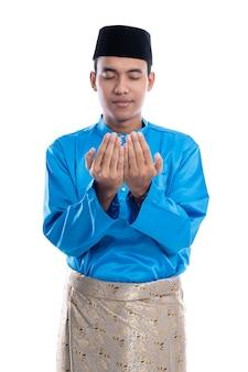白い背景の上の神に祈るヘッドキャップを持つ男性のイスラム教徒