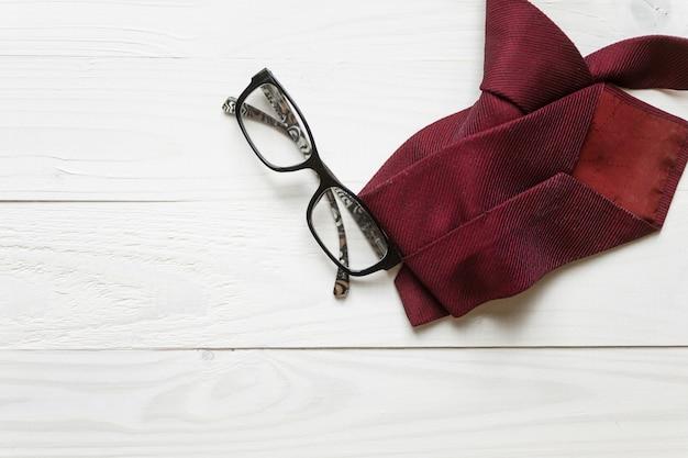 Мужской галстук и очки, лежащие на белом деревянном фоне
