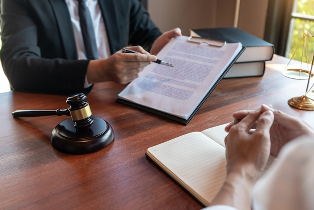 男性の公証人弁護士または裁判官が契約書に相談または話し合う