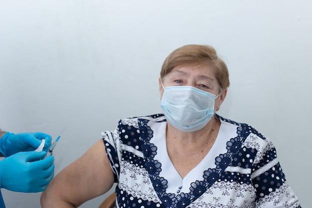 男性看護師が年配の女性に注射をする