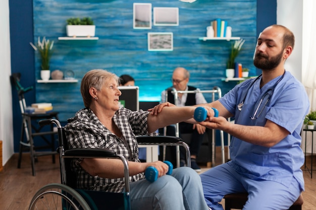 Male nurse helping senior retired disabled woman in wheelchair to rehabilitate using dumbbels