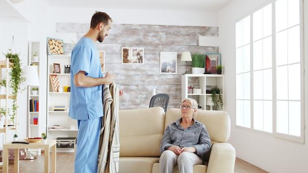 ナーシングホームに着替える年配の女性を助ける男性看護師