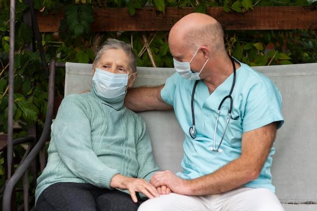 年配の女性とブランコ椅子の男性看護師