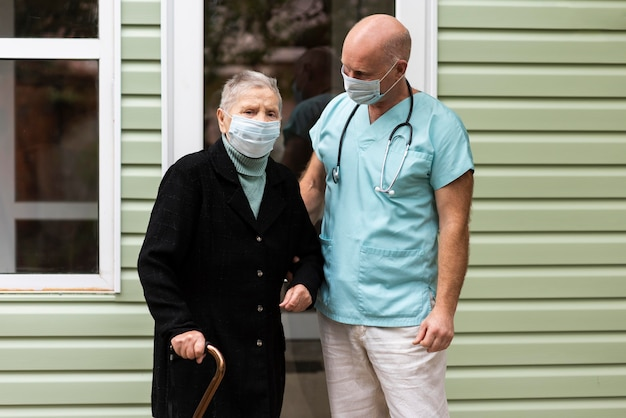 Male nurse posing with older female with cane