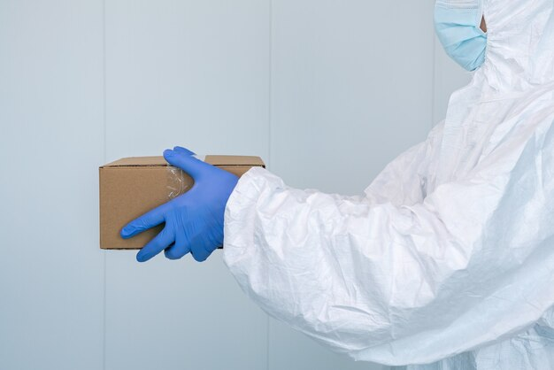 Male nurse on protective suit ppe shows a box in hospital. healthcare worker receives medical supplies to care for patients with coronavirus or covid 19. doctor wearing a ppe.
