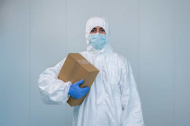 A male nurse in a protective suit ppe shows a box in the hospital. the healthcare worker receives medical supplies to care for patients with coronavirus or covid 19