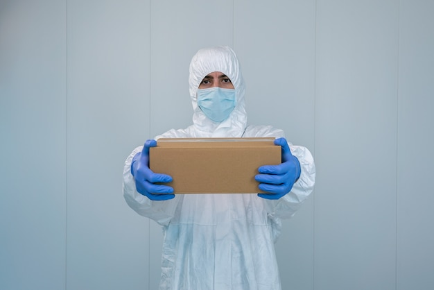 A male nurse in suit protective equipment delivers medical supplies for coronavirus or covid 19