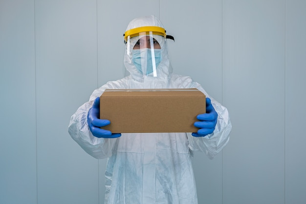 A male nurse in suit protective equipment and face shield shows a box in a hospital. healthcare worker receives medical supplies to care for patients with coronavirus or covid 19.