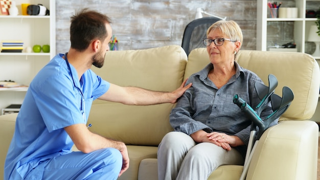 Male nurse talking with old woman suffering of parkinson in nursing home