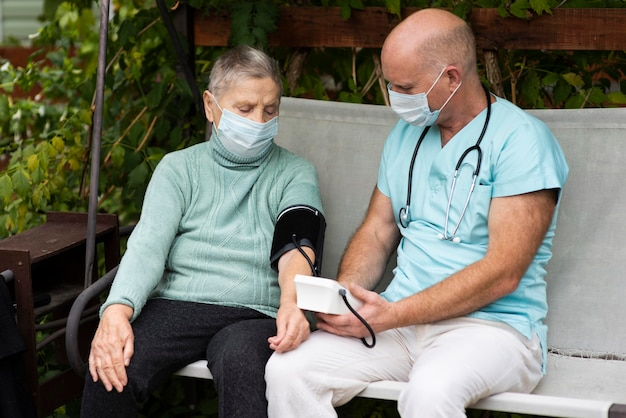 Male nurse using blood pressure monitor on older woman