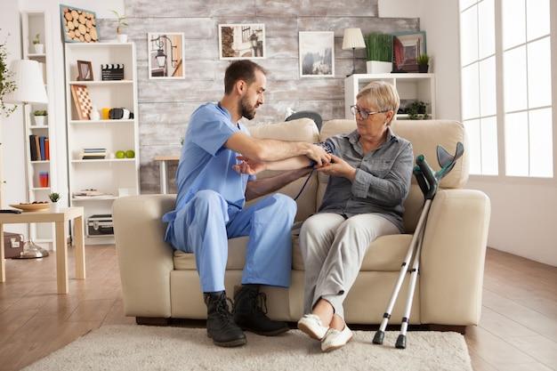 Male nurse using digital blood pressure device on senior woman in nursing home.