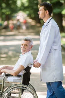 Male nurse walking with senior patient in wheelchair.