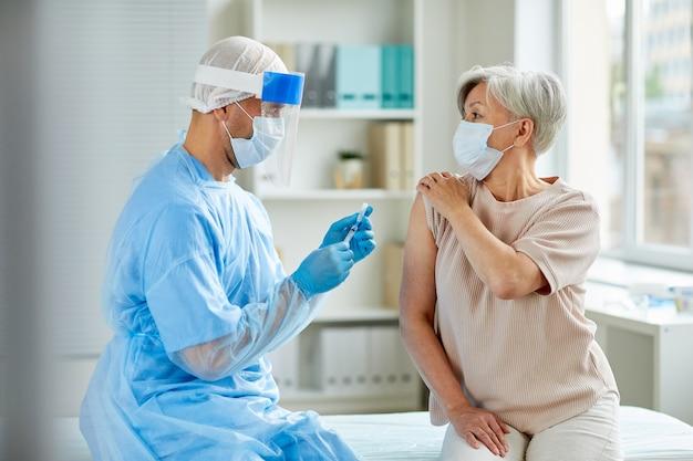 Медсестра в защитной маске и перчатках готовит медицинский шприц для инъекции пожилому пациенту
