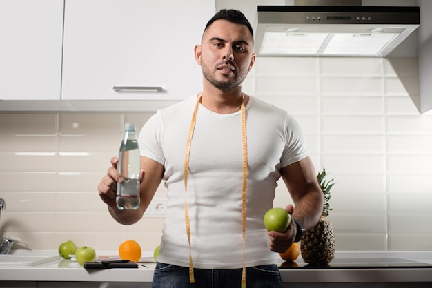 Male nutritionist keeps a bottle of water and an apple in the kitchen
