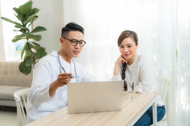 男性の産婦人科医-クリニックまたは病院のヘルスケアで若いストレス女性と一緒に働く婦人科医