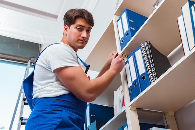 Male office cleaner cleaning shelves in office