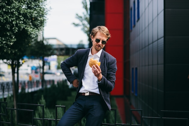 A male office worker sits outside in the summer and eats a burger