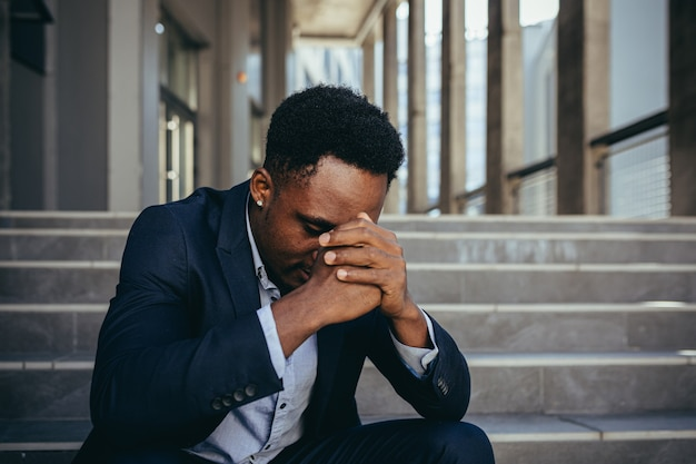 Male office worker tired after work, african american has severe headache, sitting on stairs near office
