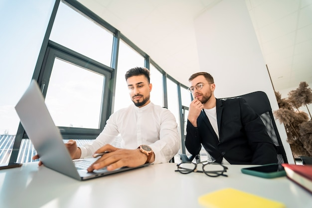Male office workers at laptop
