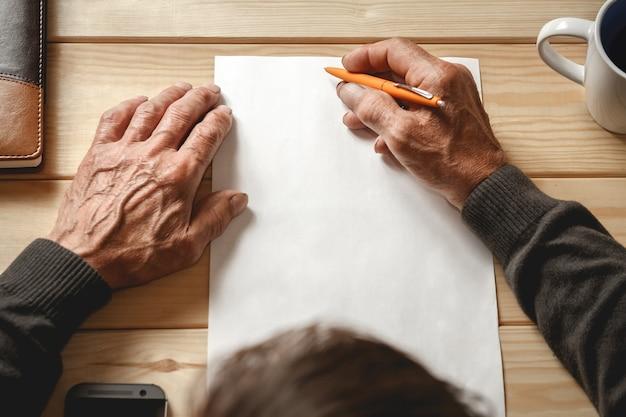Мужские старые руки пишет на чистом листе бумаги