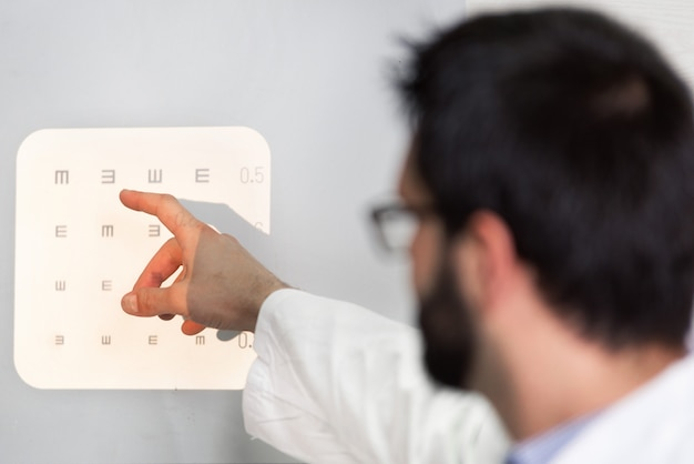 Male ophthalmologist pointing at letters of eye chart.
