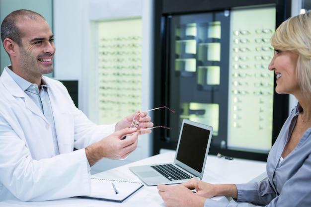 Мужской окулист разговаривает с пациенткой