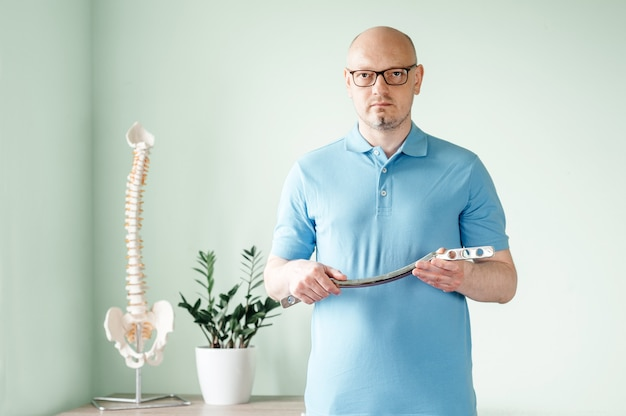 A male osteopath practitioner holding a stainless iastm treatment tool used for soft tissue treatment, snstrument assisted soft tissue mobilization and ultimate fascia release