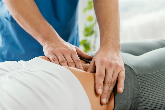 Male osteopathic therapist checking female patient's abdomen
